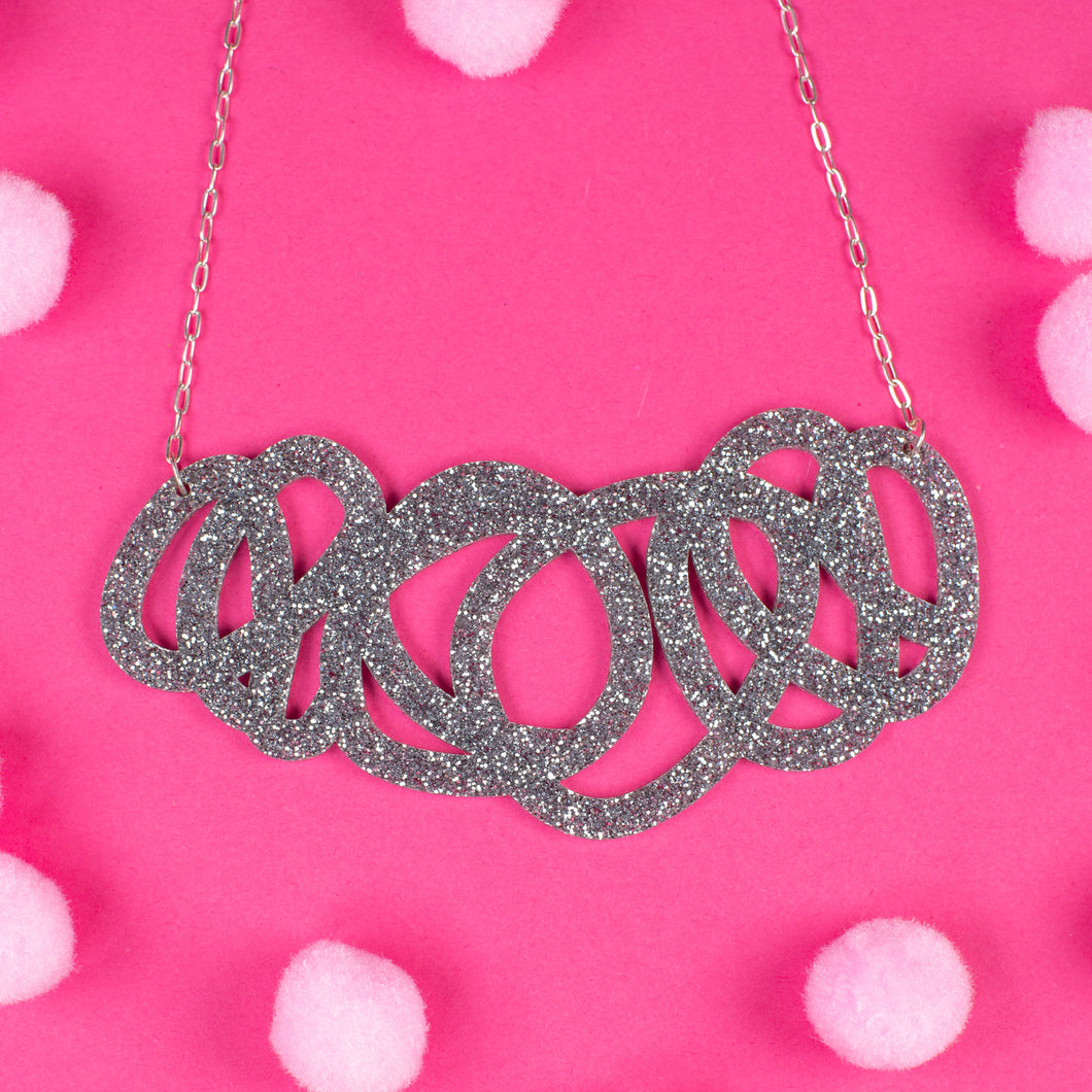 Chunky silver glitter statement necklace on pink background