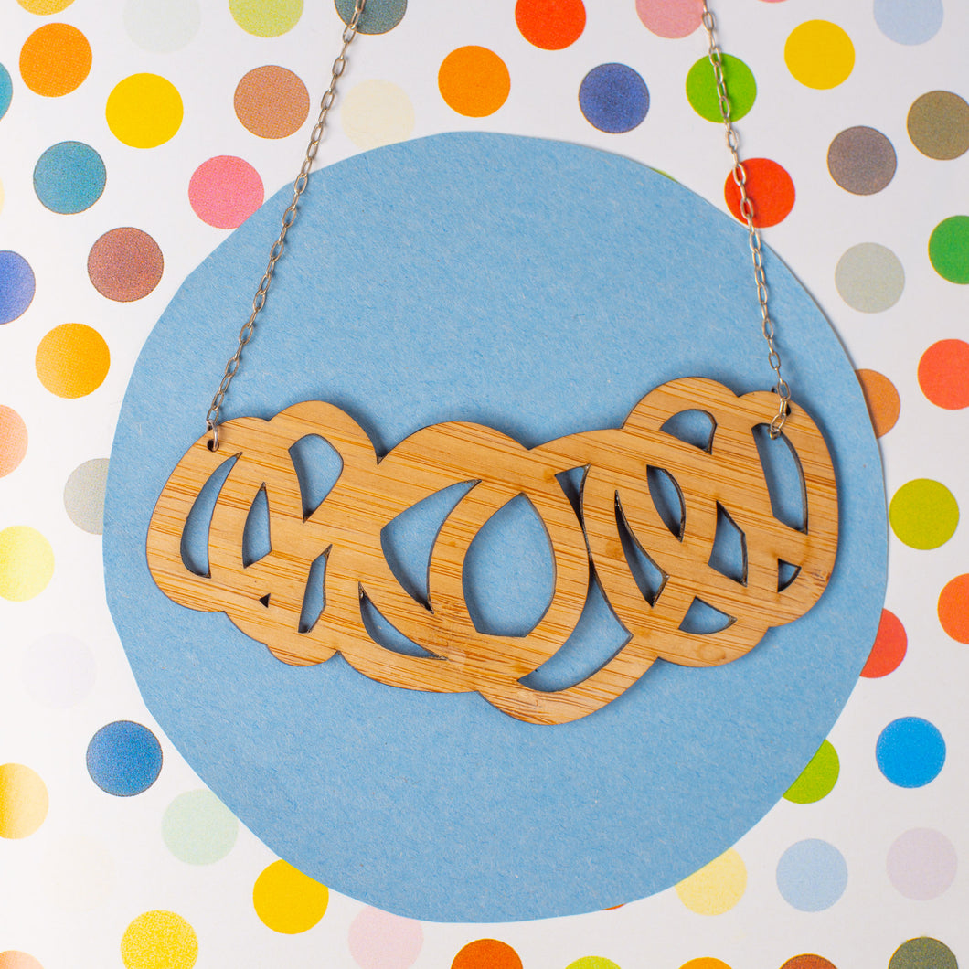 Chunky wood statement necklace shown on polka dot paper