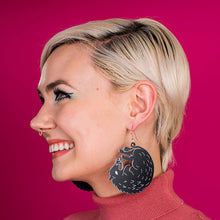 Load image into Gallery viewer, large black boar earrings on model