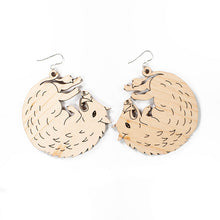 large wood boar earrings over white background