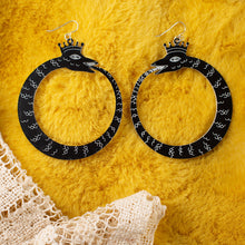 Load image into Gallery viewer, large black ouroboros earrings over yellow faux fur