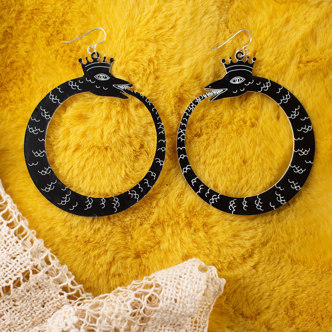 large black ouroboros earrings over yellow faux fur