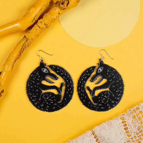 large black wolf earrings on yellow background