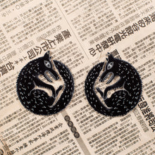Load image into Gallery viewer, large black wolf earrings on newspaper
