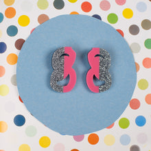 silver and pink statement stud earrings on polka dot background