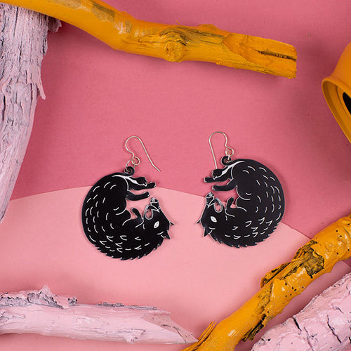 small black boar earrings styled on pink background