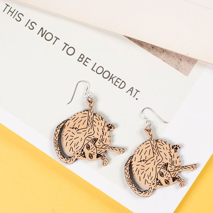 small wood cat earrings styled on magazine