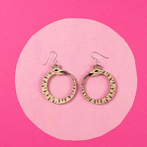 small wood ouroboros earrings styled over pink background