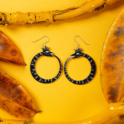 small black ouroboros earrings on yellow background