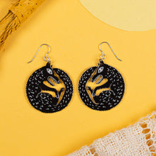 small black wolf earrings on yellow background