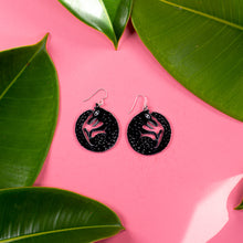 small black wolf earrings on pink background with green leaves