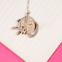 Load image into Gallery viewer, wood cat necklace styled on notebook paper