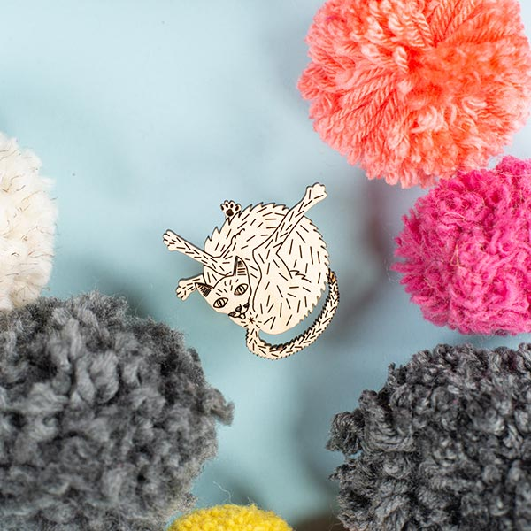 wood cat pin styled with pom poms