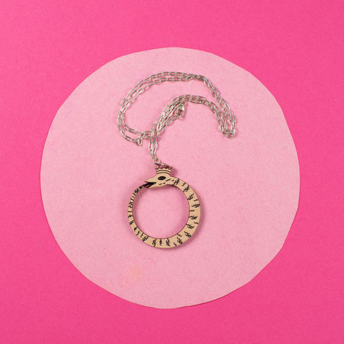 wood ouroboros necklace on pink background