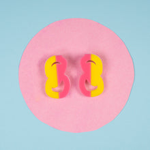 Pink and yellow statement stud earrings on pink and blue background