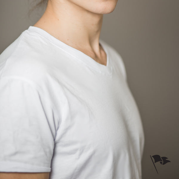 A model wearing a v-neck t-shirt made of white cotton.