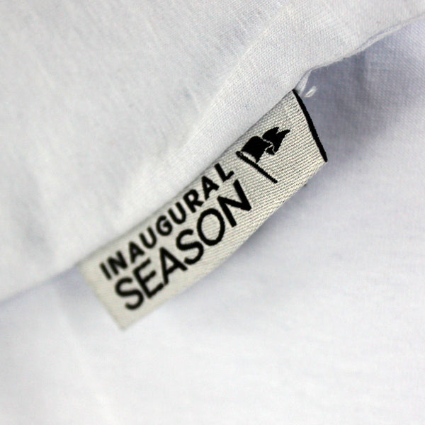Woven label on a premium, v-neck t-shirt made of white cotton.