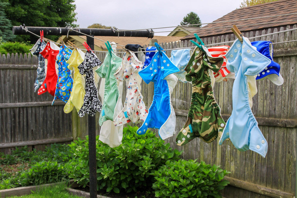 Brightly colored Charlie Banana Reusable Cloth Diapers drying on a clothes line
