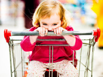 Young girl in grocery shopping cart