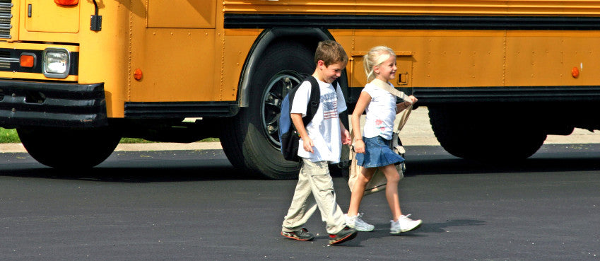 2 young children walking with a school bus in the background