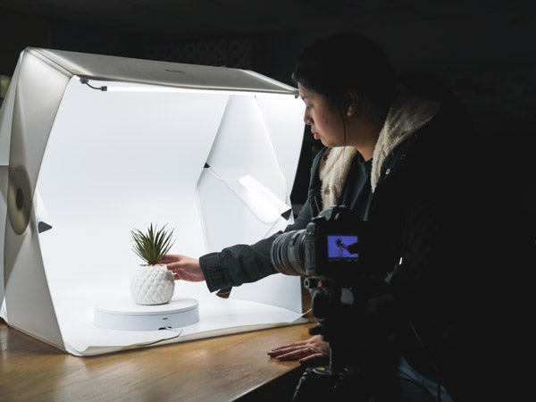 woman using the foldio light tent for product photography