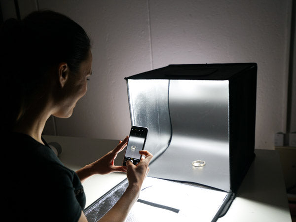woman using the hypop studio buddy light tent to photograph ring