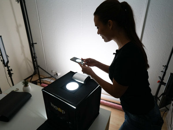 woman using the hypop studio buddy light tent to photograph jewellery