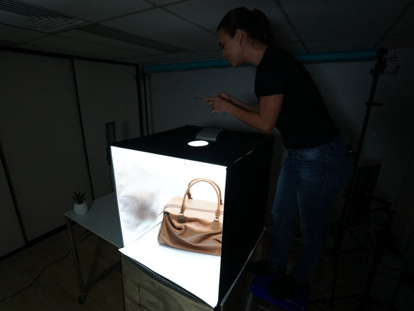 woman using the hypop studio buddy light tent to photograph handbag