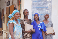 Midwives stand outside rural clinic in Senegal holding Bokk Bundle care boxes