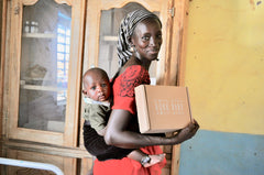 mother with baby holds Bokk Bundle care box