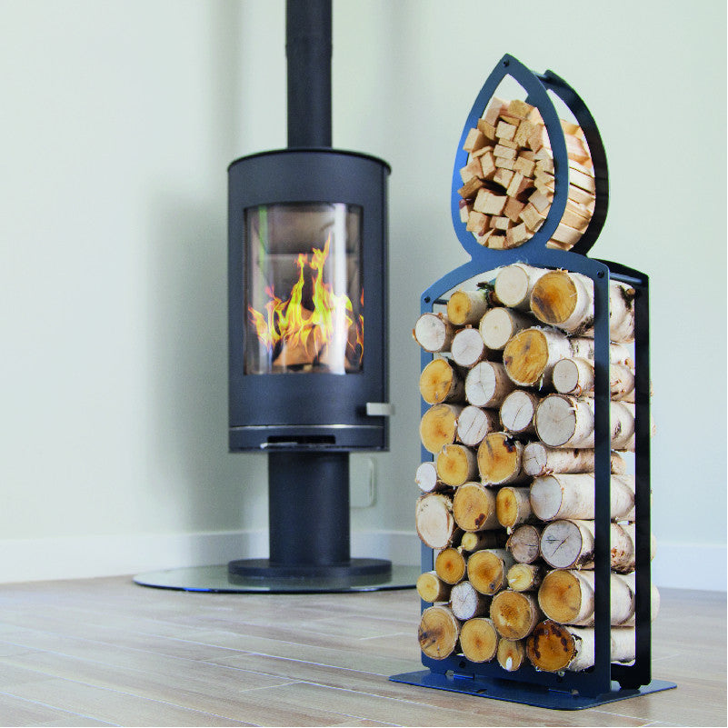 One of Ardour's candle shaped metal log baskets in jet black. It is a tall candle shape with two compartments; A small one at the top to store kindling and a large one for the main body to store the logs. Its compact design means logs can be stored in a smaller foot print than a traditional wicker basket of a similar footprint