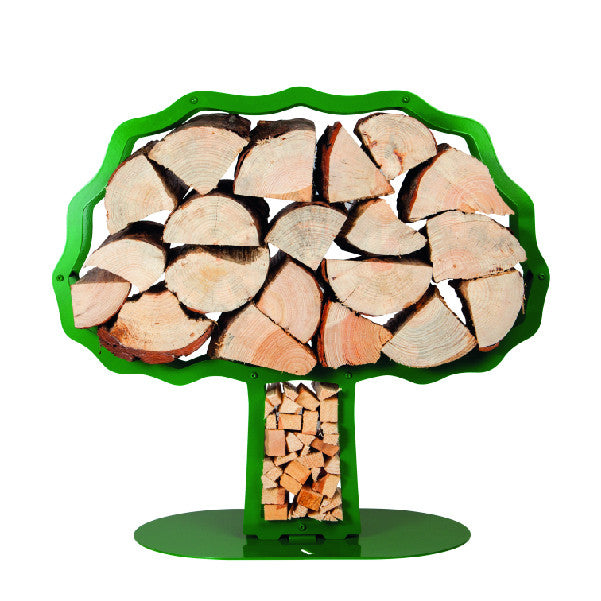 One of Ardour's Oak tree shaped metal log baskets in may-green next to a modern fire. It has a profile of an oak tree with a broad trunk and is attached to a base-plate. The design has two compartments; one in the trunk to store kindling and a large one for the main body of the tree to store the logs.