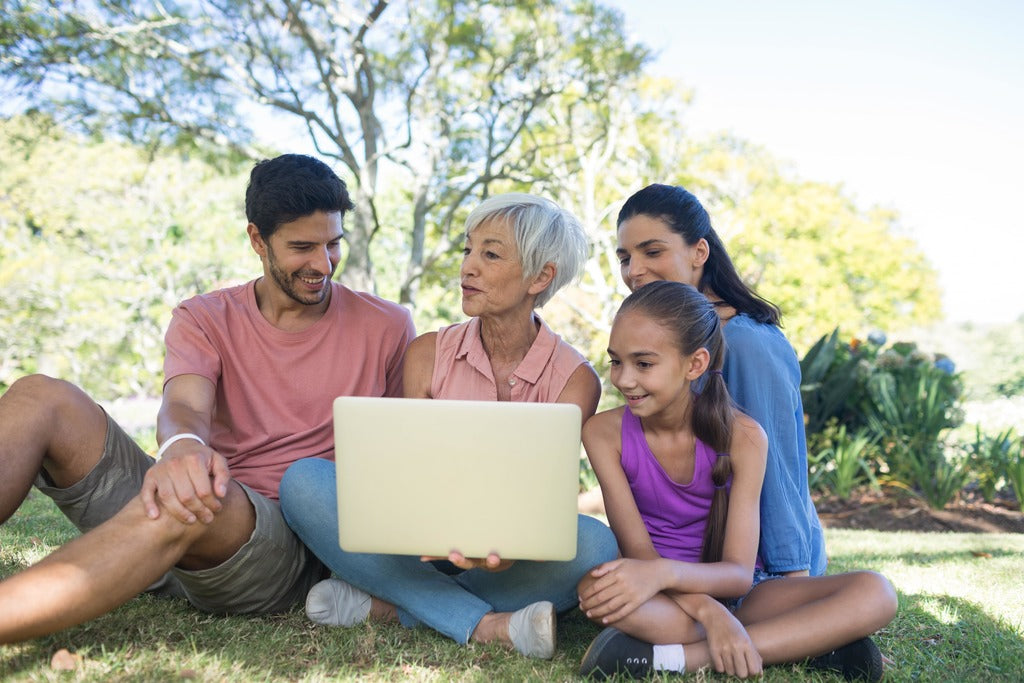 Family talking while using laptop in the park