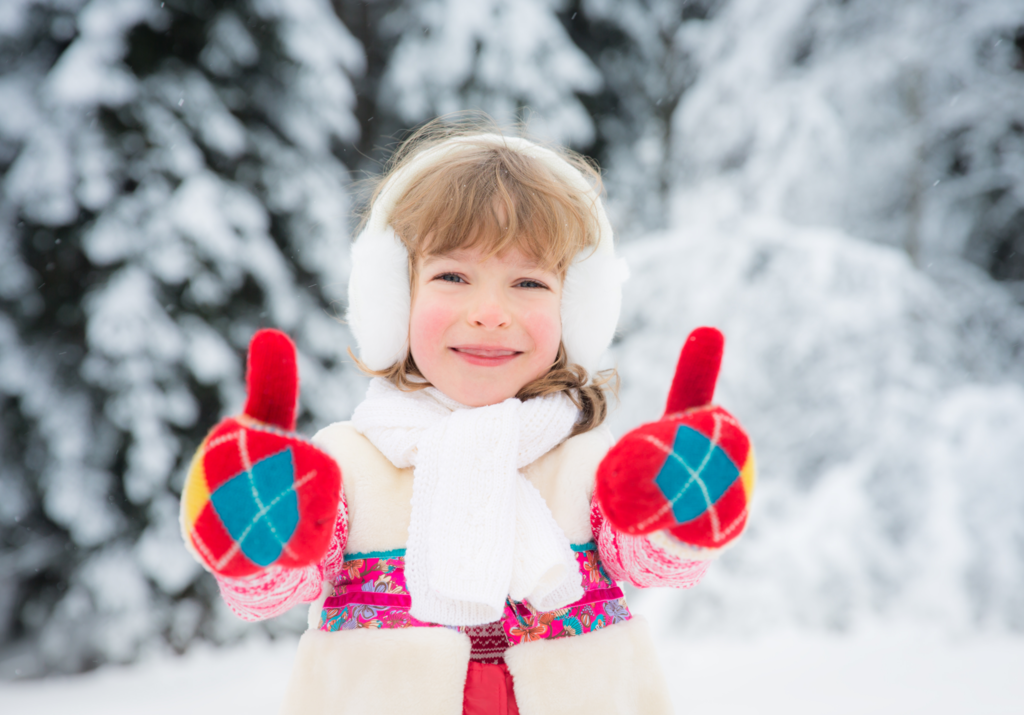 child giving a thumbs up in the snow