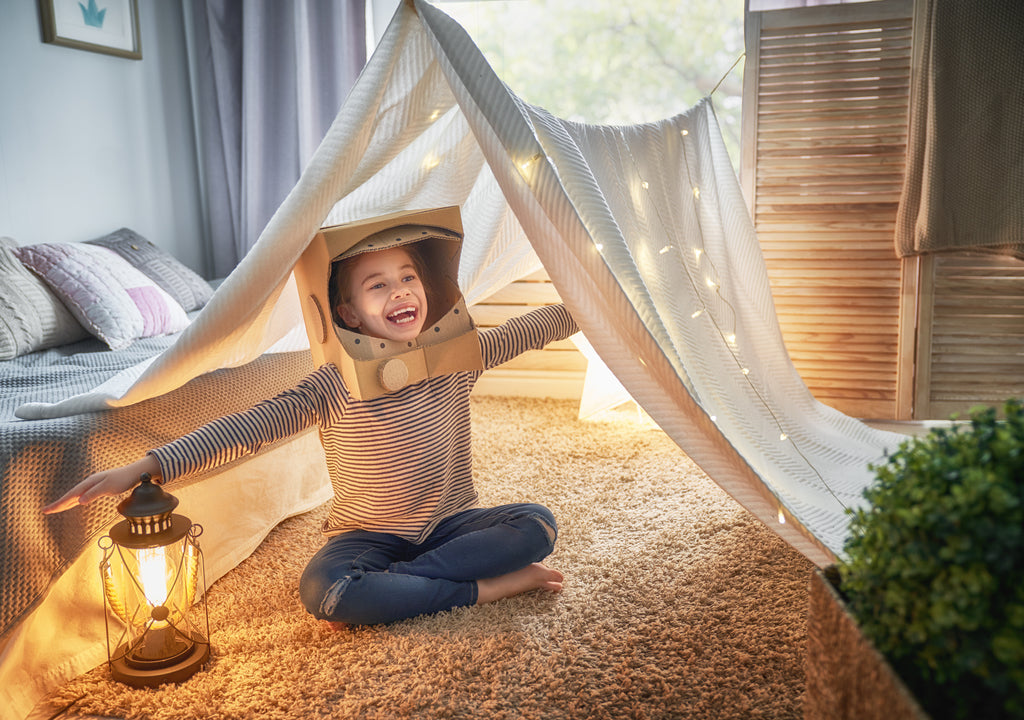 Kid playing under a sheet or tent
