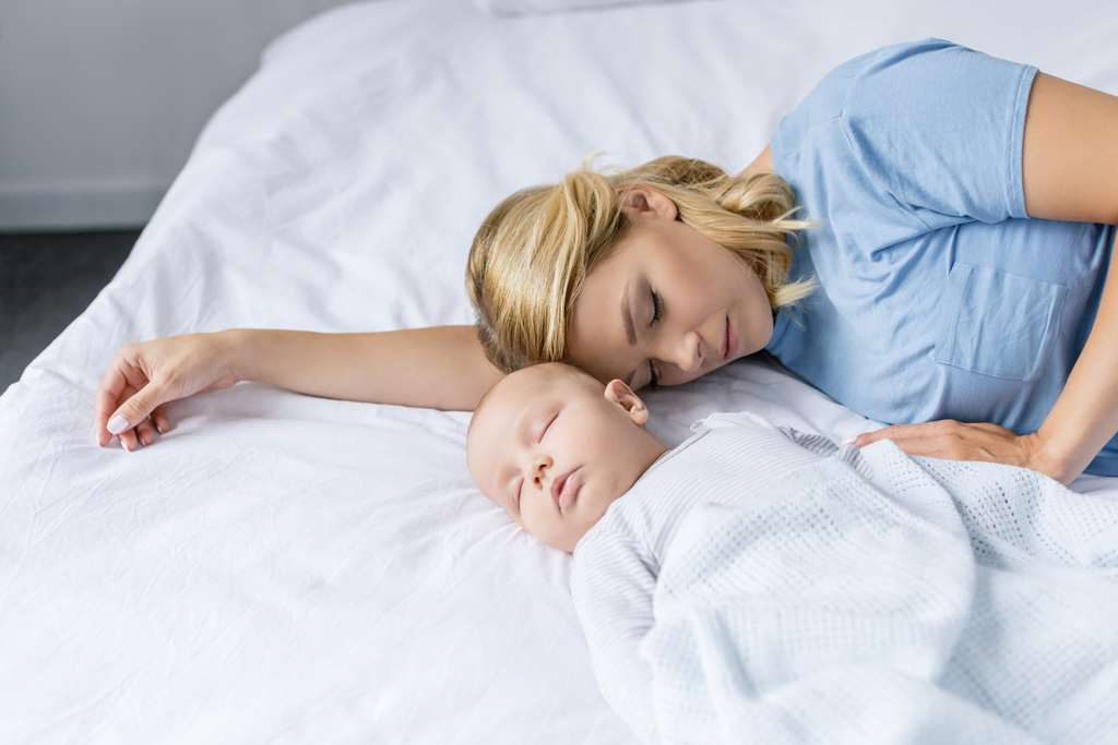 portrait of mother and infant baby sleeping on bed together