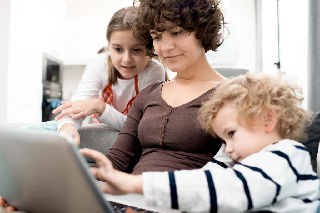 woman on a laptop with her kids