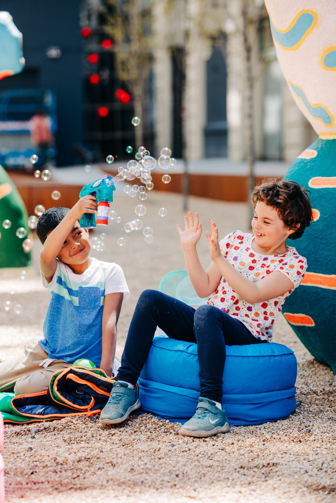 Two children sitting on a storage pouf playing outdoors with bubbles