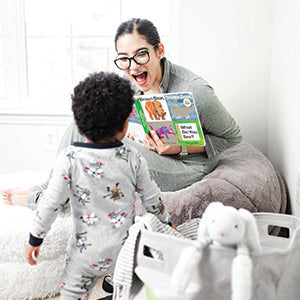 Mother playing with and reading to child while sitting on a mimish teddy bear fur bean bag chair