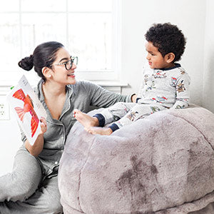 mother reading a book to her child during storytime in a playroom sitting on a beanbag