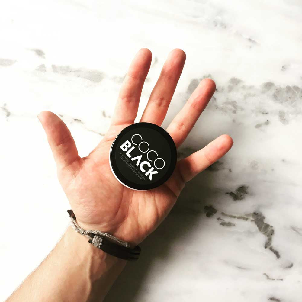 Hand Holding Activated Charcoal Teeth Whitening Powder