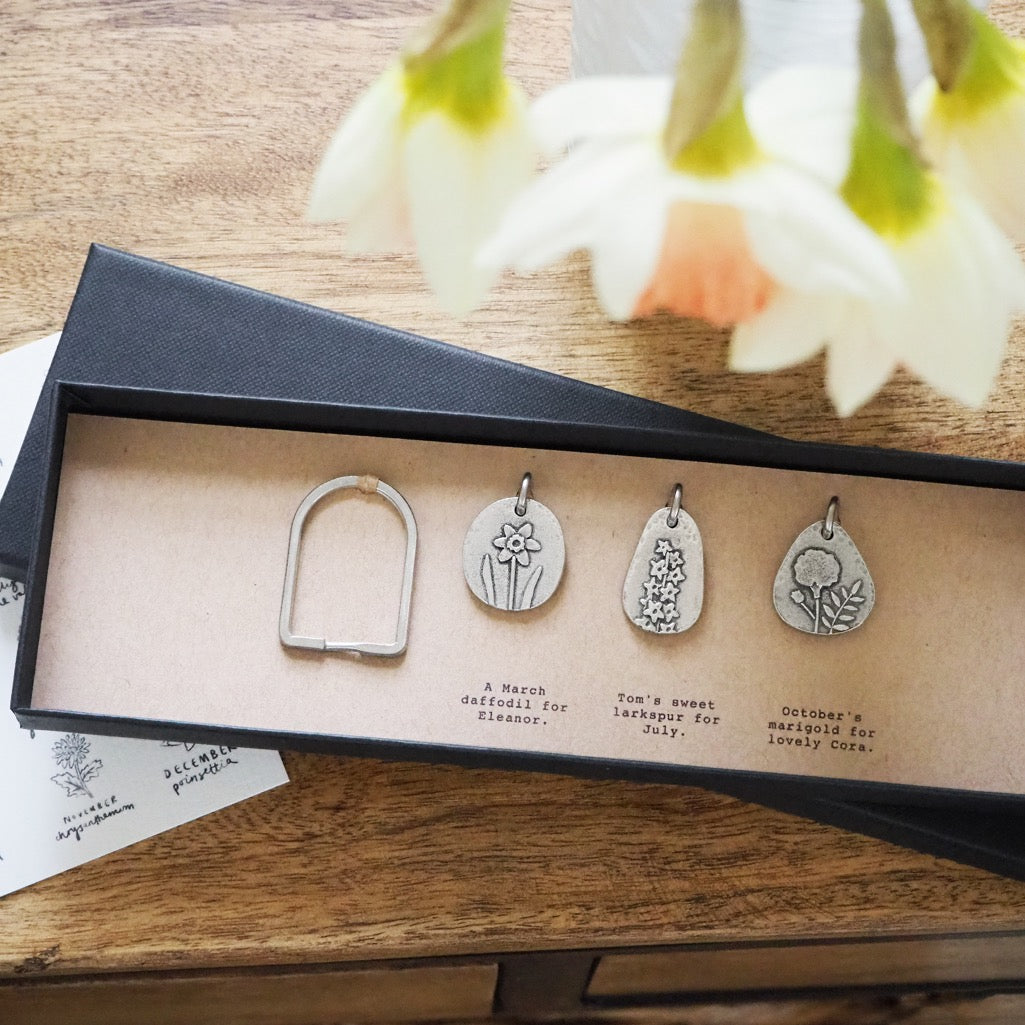 Three birth flower charms with a split ring in a long gift box.