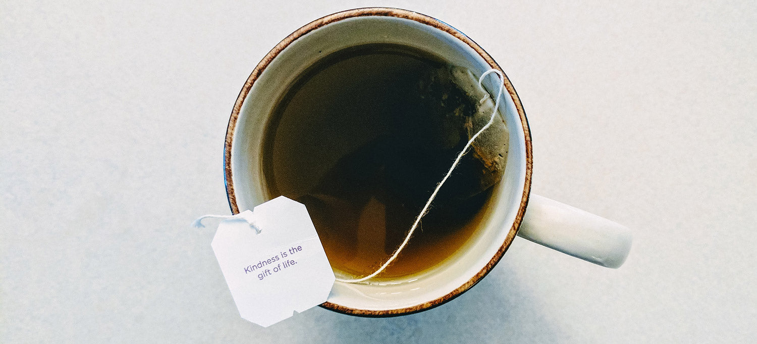coffee cup with teabag paper reading: Kindness is the gift of life