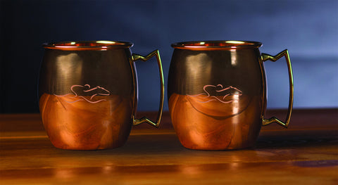 A set of 16 ounce copper mule cups with a brass handle and beautifully etched with the EMBRACE THE RACE icon.