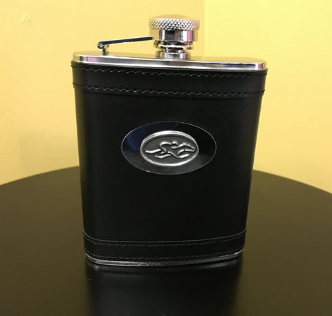 A stain steel flask wrapped in black leather.  Silver hardware and silver emblemed EMBRACE THE RACE icon center front.