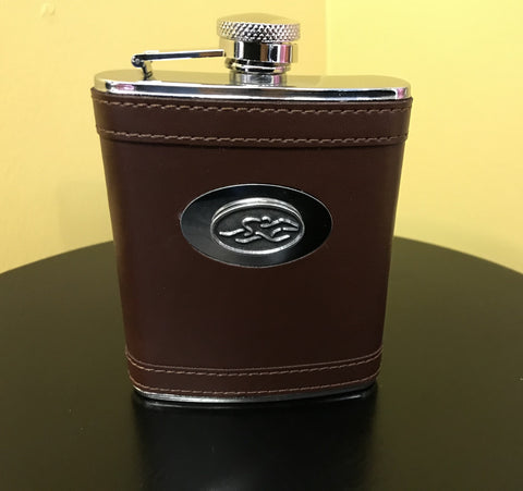 A stain steel flask wrapped in brown leather.  Silver hardware and silver emblemed EMBRACE THE RACE icon center front.