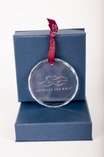 Beautiful circular glass ornament adorned with the EMBRACE THE RACE logo lightly etched.