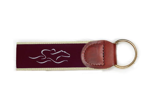 An EMBRACE THE RACE signature key fob with our signature cardinal and white ribbon on taupe backing and brown leather tab.