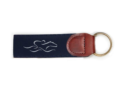 An EMBRACE THE RACE signature key fob with our signature navy and white ribbon on navy backing and brown leather tab.