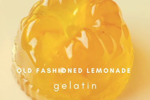 Round molded yellow gelatin dessert on a light yellow background with the words old fashioned lemonade gelatin